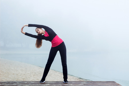 Young pretty slim fitness sporty woman does stretching exercises during training workout outdoor