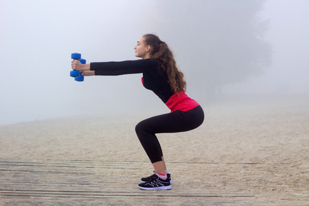 situp: Young pretty slim fitness sporty woman exercises with weights dumbells during training workout outdoor