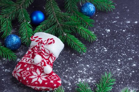 snowbound: Christmas and New Year winter holiday snowbound composition of red stocking on black space background with green fir tree branches and blue balls ornament