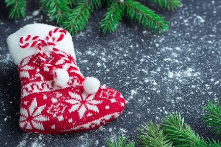 snowbound: Christmas and New Year winter holiday snowbound composition of red stocking on black space background with green fir tree branches Stock Photo