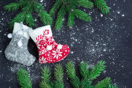 snowbound: Christmas and New Year winter holiday snowbound composition of grey and red stockings on black space background with green fir tree branches Stock Photo