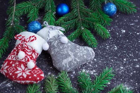 snowbound: Christmas and New Year winter holiday snowbound composition of red and grey stockings on black space background with green fir tree branches and blue balls ornament Stock Photo