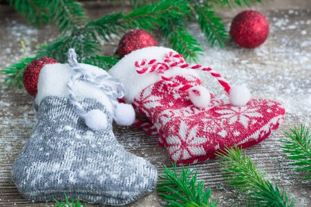 snowbound: Christmas and New Year winter holiday snowbound composition of stockings on wooden space background with green fir tree branches and balls ornament