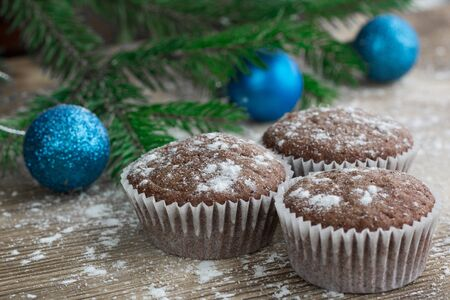 teacake: Christmas and New Year winter holiday composition of three cakes on snowbound wooden space background with green fir tree branches  and blue ball ornament Stock Photo