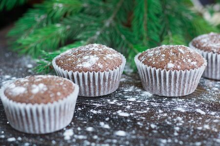 teacake: Christmas and New Year winter holiday composition of three cakes on snowbound wooden space background with green fir tree branches Stock Photo