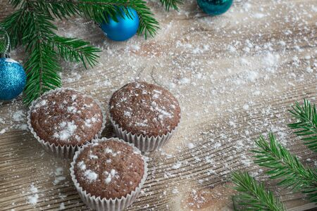 snowbound: Christmas and New Year winter holiday composition of three cakes on snowbound wooden space background with green fir tree branches  and cyan ball ornament