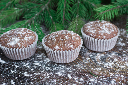 snowbound: Christmas and New Year winter holiday composition of three cakes on snowbound wooden space background with green fir tree branches Stock Photo