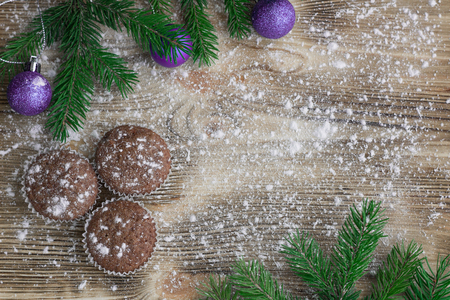 teacake: Christmas and New Year winter holiday composition of three cakes on snowbound wooden space background with green fir tree branches  and purple ball ornament