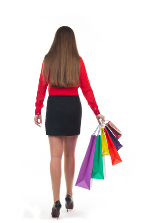 Long-haired young woman wearing red blouse and short black skirt and high hills from her back holds colourful shopping paper bags