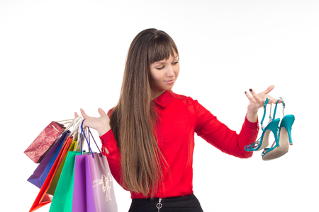 comprando zapatos: Young long-haired woman holds her purchases, many colorful paper bags, packages, and shoes in her hands after shopping Foto de archivo