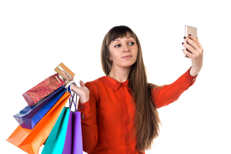 Young woman shopping with credit card holding colourful paper bags and packages does selfie Stock Photo