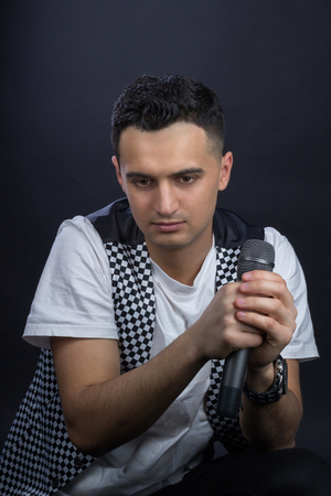 Young black-haired man dressed in black and white poses singing to microphone