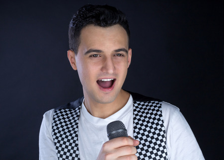 Young black-haired man dressed in black and white performs singing to microphone Stock Photo
