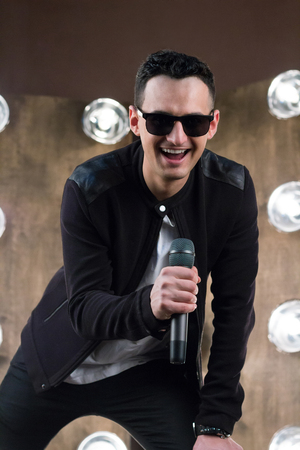Male singer of rock or pop music dressed in black and sunglasses with microphone performs on scene with lightening projectors on background