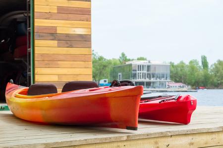 boatman: Two kayak boats on wooden deck at kayak station near river bank Stock Photo