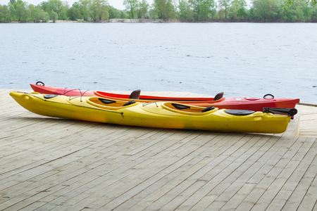 Two kayak boats on wooden deck at kayak station near river bank Stock Photo
