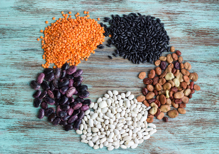 Circle of batches of yellow lentils, white, purple, brown kidney haricot beans scattered on light wooden background