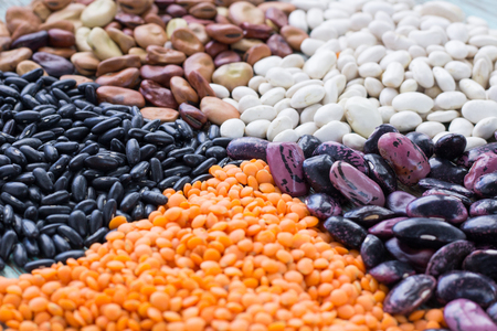 Batches of yellow lentils, white, purple, brown kidney haricot beans scattered close-up