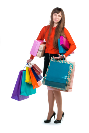 Young long-haired woman stands with many colorful paper packages and boxes in her arms after shopping
