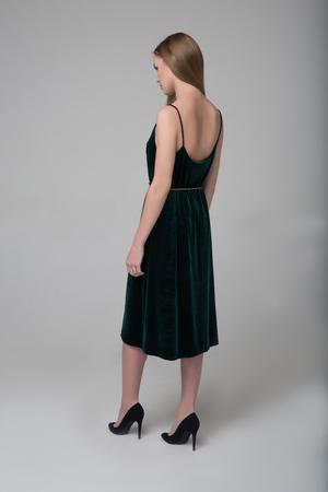 Young beautiful long-haired girl walks away in dark green dress
