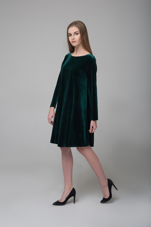 Young beautiful long-haired female model in dark green short dress