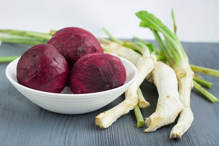 Still life of prepared cleaned raw vegetables beetroot and horseredish for borsch beet soup of russian cuisine on grey wooden background