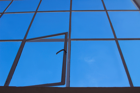 Blue sky view through big loft upper window with transparent glass cells and open leaf