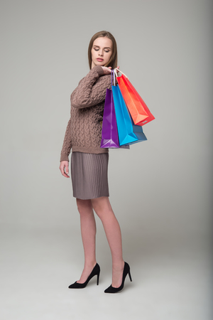 Young model long-haired blond girl in grey brown beige skirt and jamper stands holding multicolored shopping packages