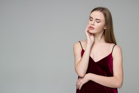 Young model long-haired blond girl in dard red dress poses showing emotions