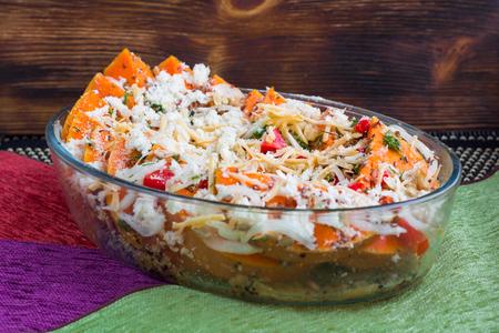 Vegetarian salad of orange pumkin, mixed vegetables, herbs and cheese