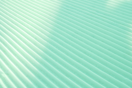 Background of diagonal geometrical parallel stripes of snow colored with light shade