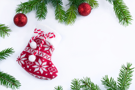 Red Christmas stocking sock and decoration balls on white background, frame of green contiferous fir tree braches