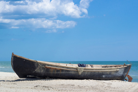 Small wooden boat with fishing nets drying on white sandy beach near sealine