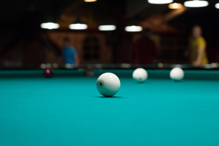 Close-up of Russian billiards game in club in process: three white balls on green game table cloth and players on background