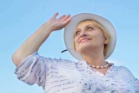 Happy smiling elderly retired lady woman watches sky holding her white hat