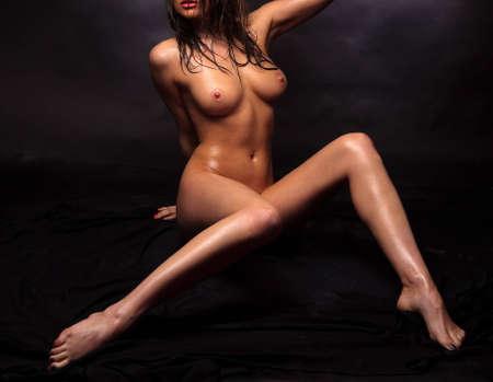 hot breast: Обнаженная девушка, покрытая каплями воды на черном фоне