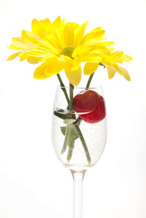 fresh graduate: Yellow flower and cherries in a glass on a white background  Stock Photo