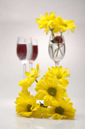 Yellow flowers and cherries in a glass on a gray background  photo