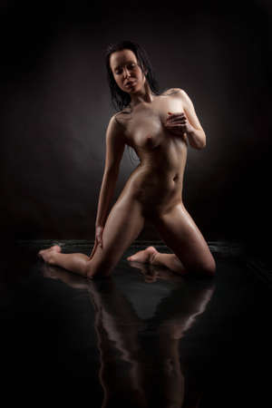 Naked girl in water on a black background photo