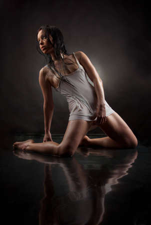 A girl in a wet t-shirt on a black background photo