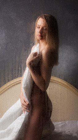 sauna nackt: Sch�ne nackte M�dchen sitzen im Bett hinter nassen Glas. Lizenzfreie Bilder