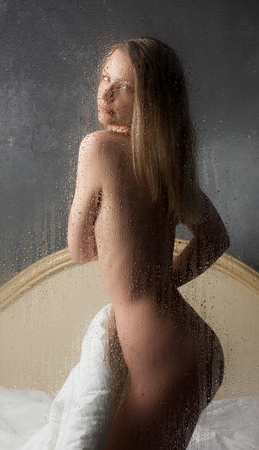 sauna nackt: Schöne nackte Mädchen sitzen im Bett hinter nassen Glas. Lizenzfreie Bilder