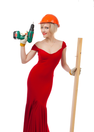 Beautiful blonde in a red dress with an electric drill and a construction helmet on a white background.