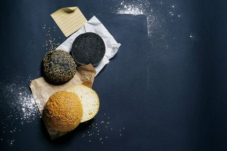 top view of two black and white burger rolls on a black background with sesame and flour