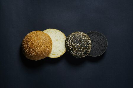 top view of two black and white burger rolls on a black background