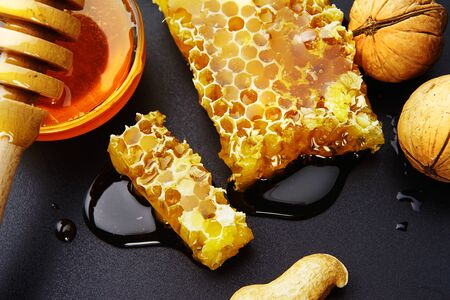 top view, honey bee flows out of honeycomb on a black background, wooden spoon for honey and nuts
