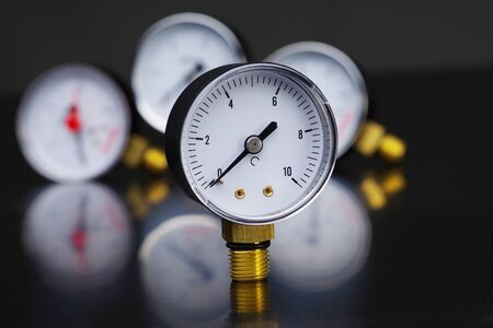 Dark surface with a deep reflection of pressure gauges.manometer in focus. A pressure gauge on the background of other instruments. Stock Photo