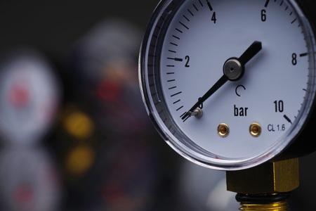 Superficie oscura con un profundo reflejo de manómetros. Manómetro en foco. Un manómetro en el fondo de otros instrumentos. Foto de archivo