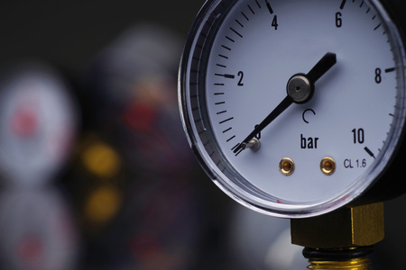 Dark surface with a deep reflection of pressure gauges.manometer in focus. A pressure gauge on the background of other instruments. Foto de archivo
