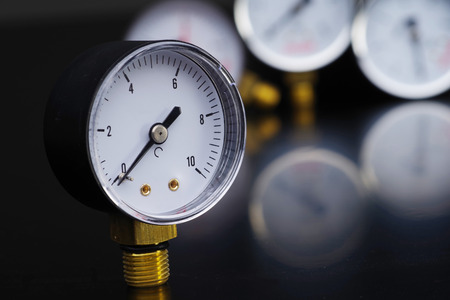 Dark surface with a deep reflection of pressure gauges.manometer in focus. A pressure gauge on the background of other instruments. Stock fotó